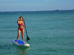 beautiful girl standing on inflatable SUP