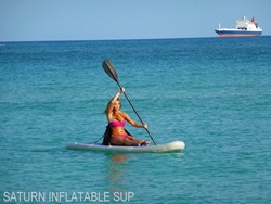 Girl kayaking while sitting on top of inflatable paddel board