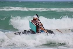 Surfing waves while sitting in a comfy beach chair.