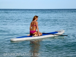 Girl kneeling on top of inflatable sup