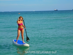 Girl enjoy riding inflatable paddle board SUP