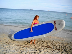 Girl holding inflatable SUP paddle board ready to go paddling